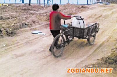 一位村民推着装着水桶的三轮小车回家
